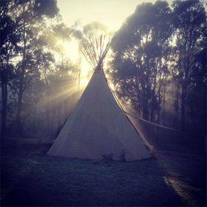 Teepee at sunrise with sun rising from behind